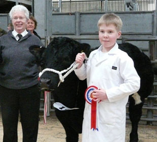 Connor receives Champion Male rosette from judge Morag Cartney